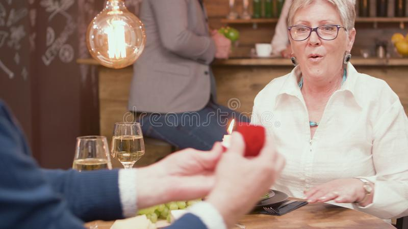 Enthusiastic senior woman when her husband is giving her a ring with diamonds royalty free stock photography