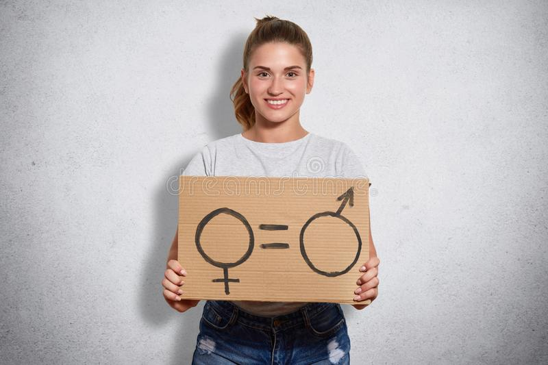Enthusiastic smart young feminist smiling sincerely, looking directly at camera, holding signs denoting women and men sex, having. Enthusiastic smart young stock photos