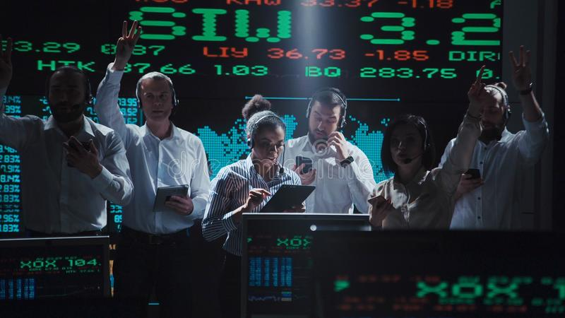 Enthusiastic stock broker team in live office. An enthusiastic stock broker team in a futuristic office full of live global market feeds stock photography