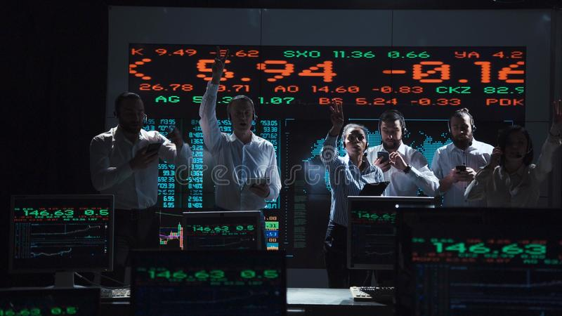 Enthusiastic stock broker team in live office royalty free stock photography