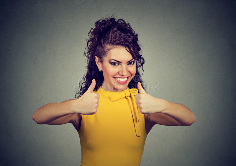 Enthusiastic woman giving thumbs up gesture of approval and success stock photography