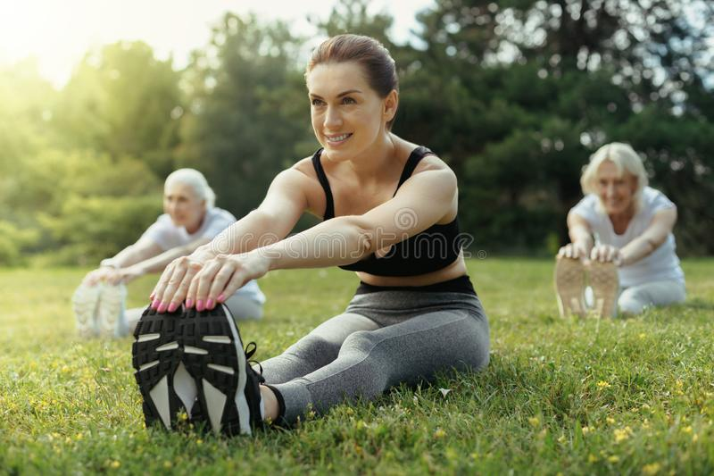 Enthusiastic woman training group of retired people stock photo
