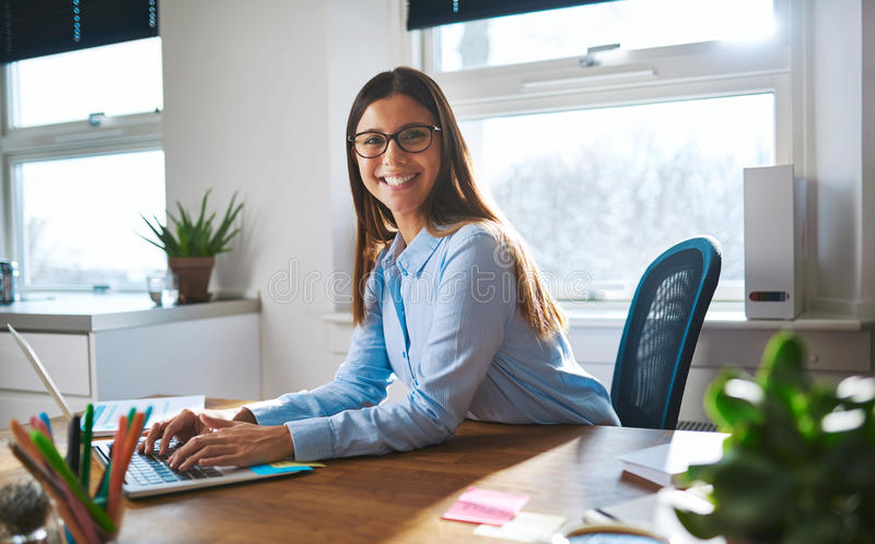 Enthusiastic woman working at desk royalty free stock image