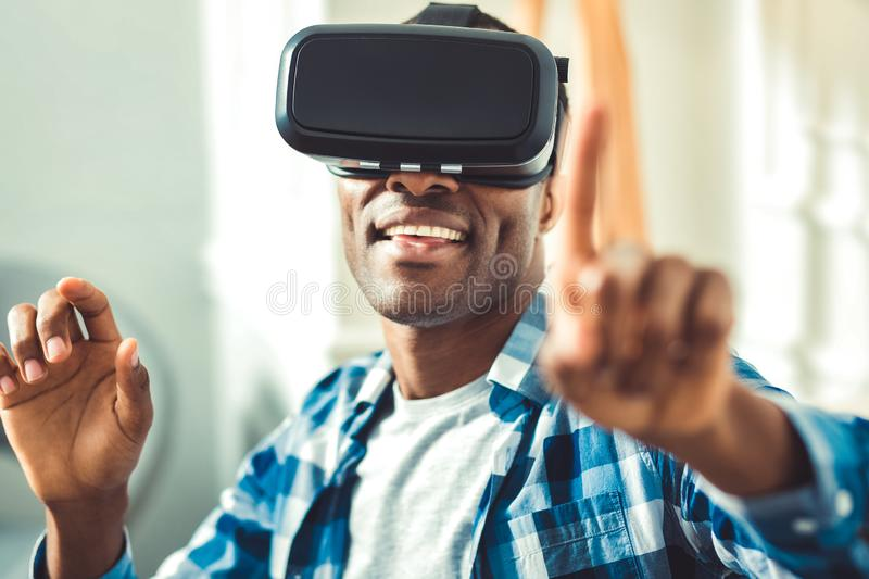 Enthusiastic young afro american man changing image. VR landscape. Vigorous afro american man putting on VR glasses and opening app stock image