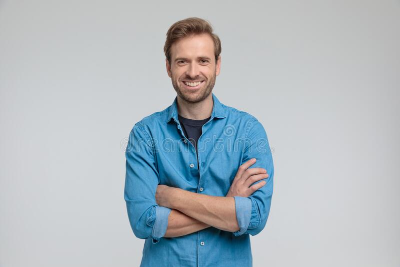 Enthusiastic young casual man crossing arms and smiling stock photo