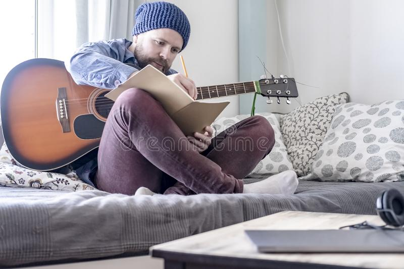 Enthusiastic male composer, writing down music in his notebook and holding an acoustic guitar, sitting on a sofa, in a comfortable. Enthusiastic young male royalty free stock photography