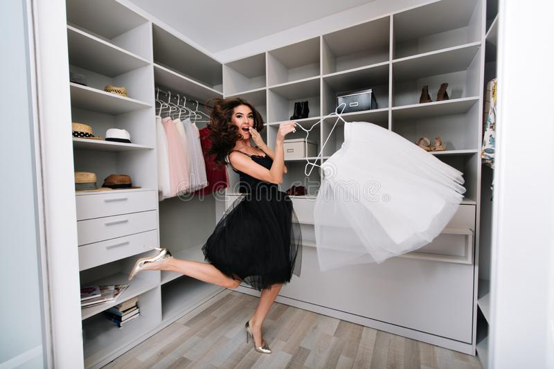 Enthusiastic young woman jumping in dressing room, nice wardrobe with skirt in hands. She`s happy with the choice. She`s royalty free stock images