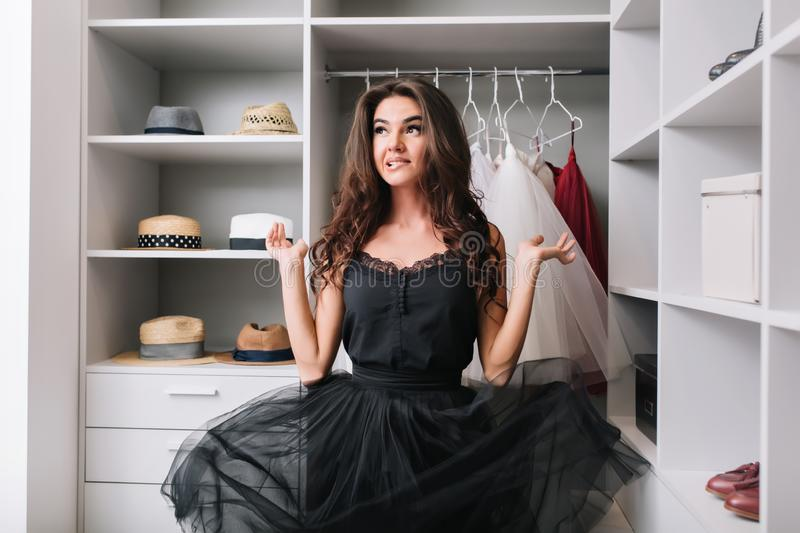 Enthusiastic young woman standing in dressing room, wardrobe and thinking, has contemplative look. Her beautiful black. Dress hovers in the air. She has long royalty free stock image