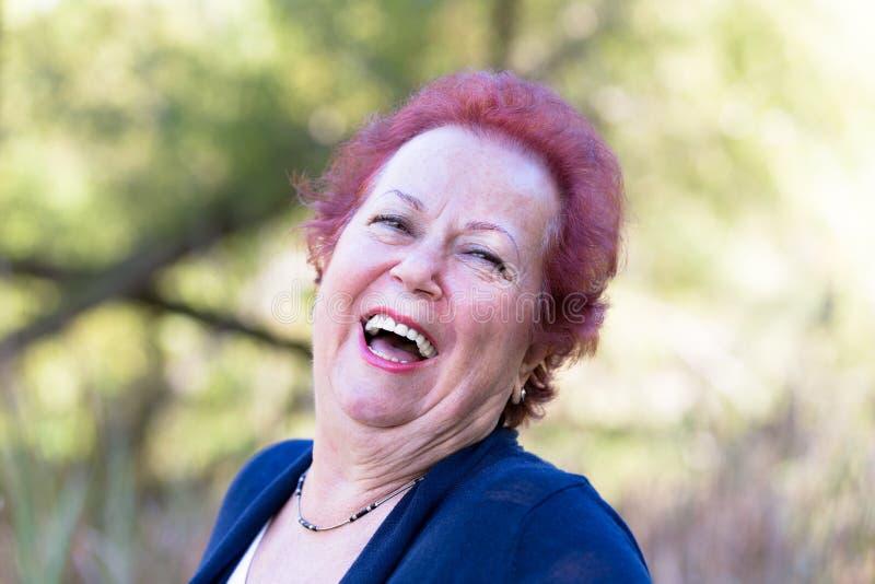 Enthusiastische ältere Frau, die ein echtes Lachen gibt lizenzfreie stockfotografie