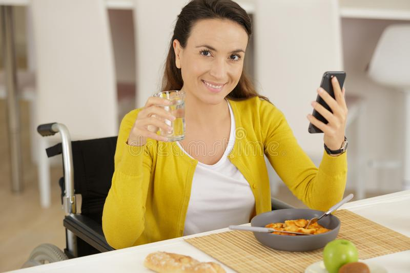 Enthusiastische behinderte Frau unter Verwendung des Smartphone beim Frühstücken stockfoto