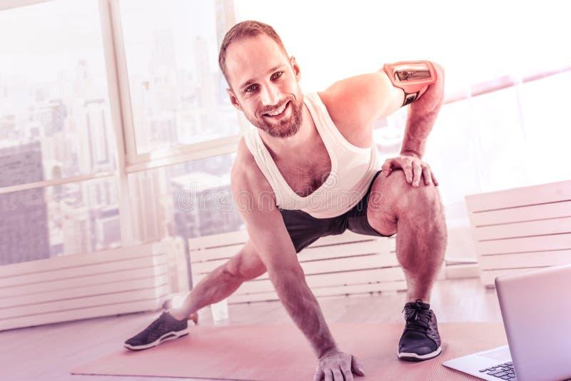 Enthusiastischer Trainer, der zu Hause Übungen vor der Kamera tut stockfoto