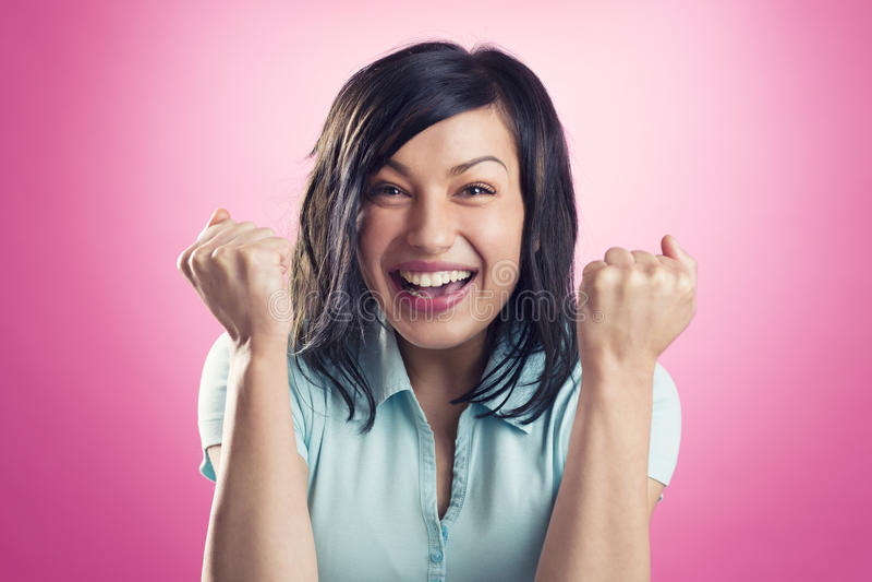 Enthusiastisches glückliches Mädchen mit den Fäusten oben lizenzfreies stockbild