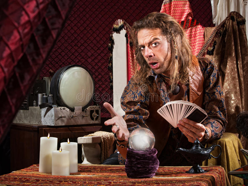 Enticing Fortune Teller. Enticing man with tarot cards and crystal ball royalty free stock photos