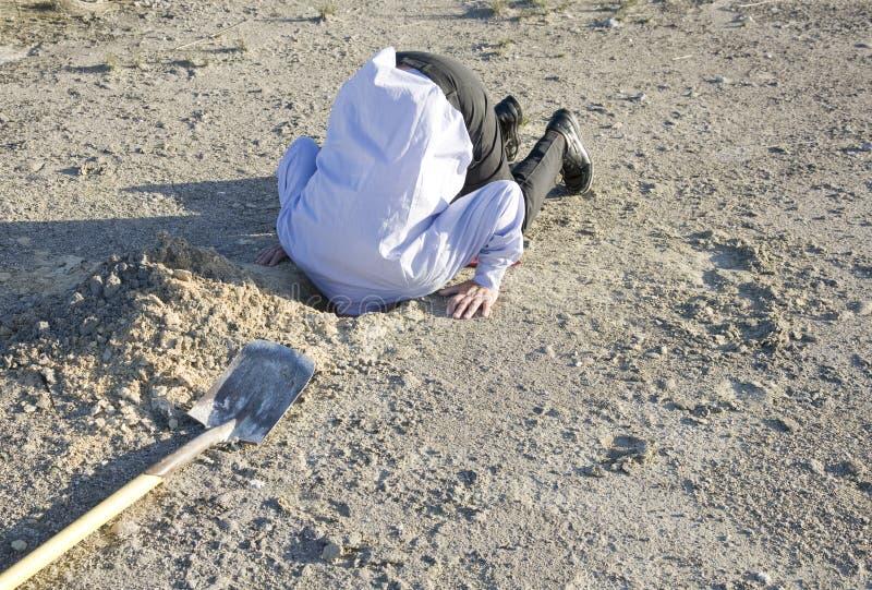 Entierre su cabeza en la arena foto de archivo