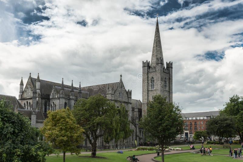 Entire Saint Patrick Cathedral and park, Dublin Ireland. Dublin, Ireland - August 7, 2017: Gray stone bell tower, nave and chancel of Saint Patrick Cathedral royalty free stock photos