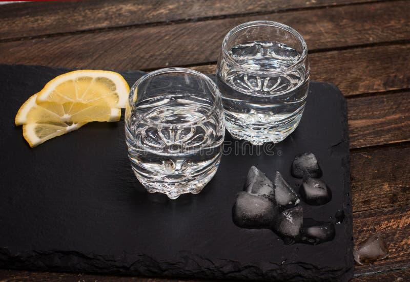 Entkörnen Sie Stärkungsmittel, Wodka, oder Rum mit Eis und Zitrone auf Schieferbrett flehen an an lizenzfreie stockbilder