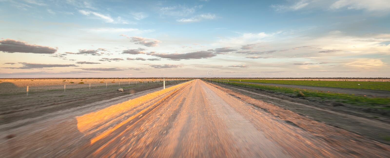 Entlang einen geraden Schotterweg bei Sonnenuntergang schnell fahren lizenzfreie stockfotografie