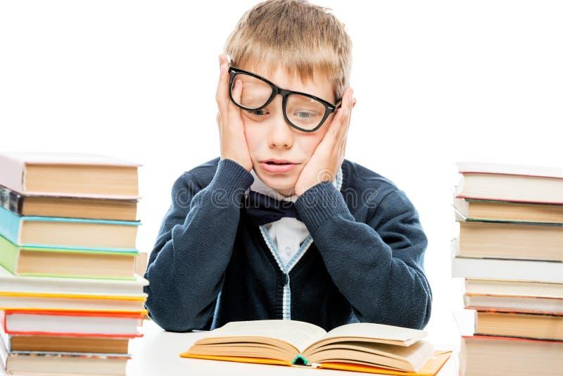 Entmutigter Schüler unter einem Stapel von Büchern auf einem weißen backgroun lizenzfreies stockbild