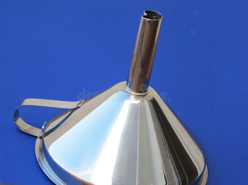 Entonnoir métallique devant un fond bleu avec des réflexions en turquoise argentée photos stock