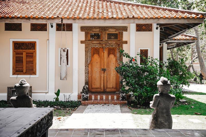Entrée à la maison jaune Vieille porte en bois avec les mod?les d?coup?s Chemin en pierre menant à une porte verrouillée photographie stock libre de droits