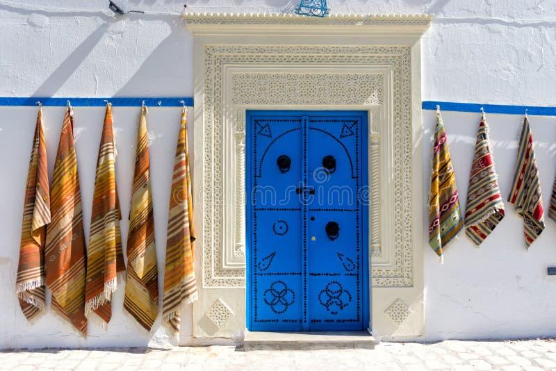 Entrée avec la porte colorée et tapis dans Kairouan, Tunisie photographie stock libre de droits