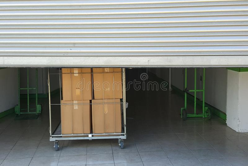 Entrée dans des unités de stockage d'individu, grand chariot avec des boîtes dans l'avant, porte en métal photo stock