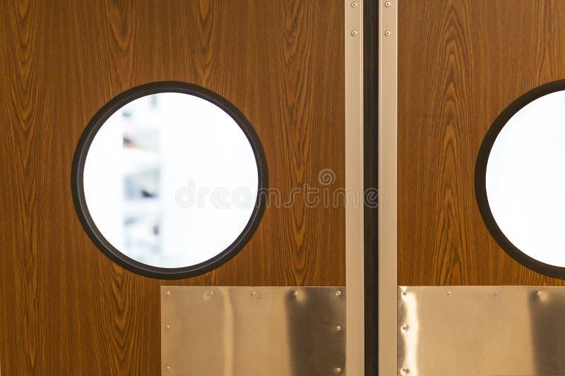 Entrée de cuisine de restaurant Porte à deux battants en bois fermée avec la fenêtre ronde de style de hublot Vérité de café à l' image libre de droits
