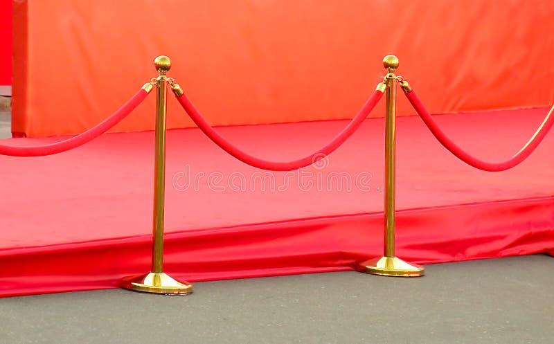 entrée de tapis rouge avec les supports et les cordes d'or Candidats de célébrité à présenter en première Étoiles sur l'attributi photos libres de droits