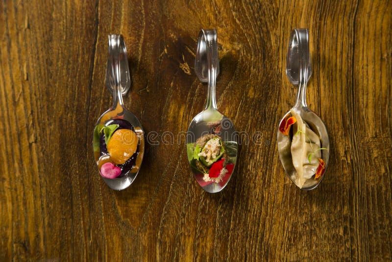 Entrée, entrée et dessert de repas sur le pouce dans une cuillère image stock