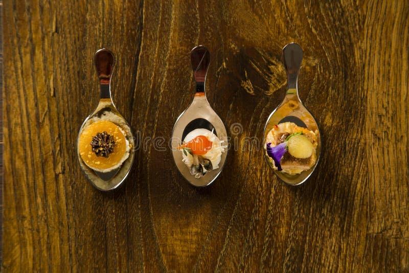 Entrée, entrée et dessert de repas sur le pouce dans une cuillère image libre de droits