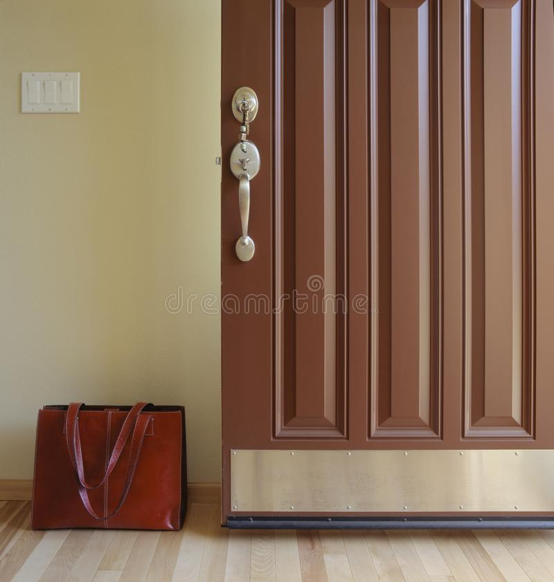 Entrée principale ouverte de maison avec le bref sac de serviette dans l'entrée Venez à la maison de ou partir pour le concept de photos libres de droits