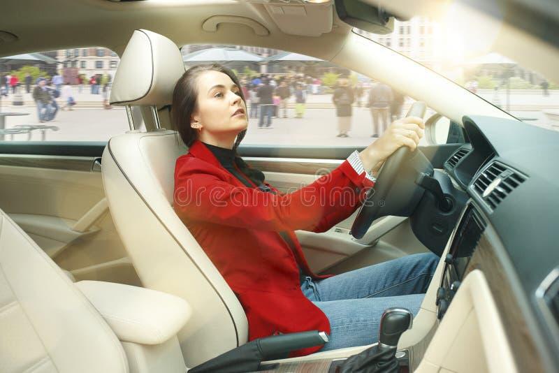 Entraînement autour de la ville Jeune femme attirante conduisant une voiture image libre de droits