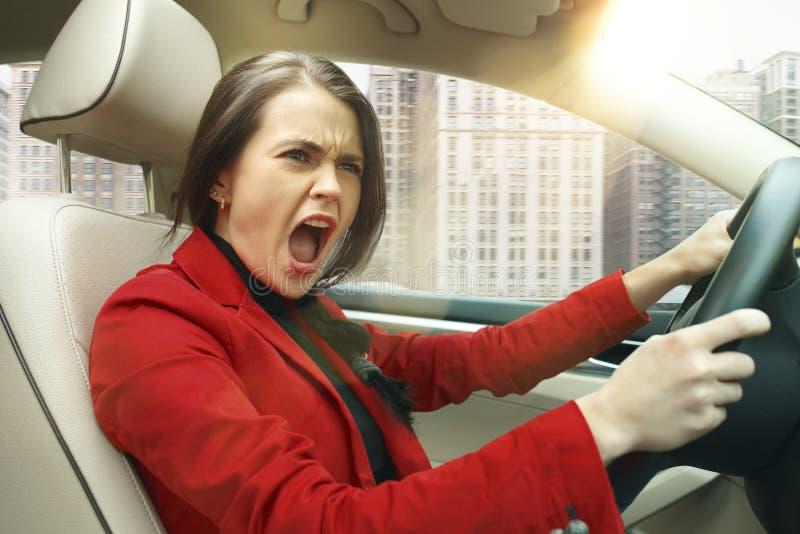 Entraînement autour de la ville Jeune femme attirante conduisant une voiture photo stock