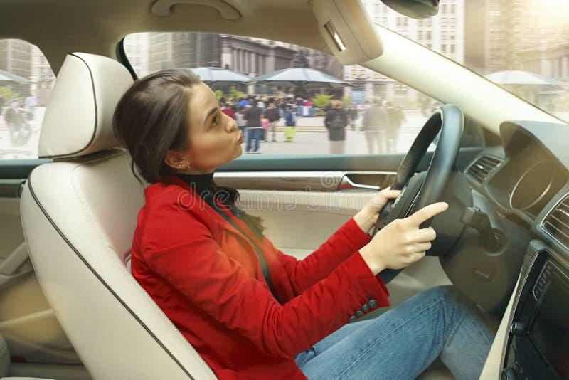 Entraînement autour de la ville Jeune femme attirante conduisant une voiture photographie stock