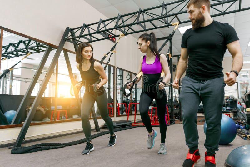 Entraînement d'entraîneur de forme physique et femmes de aide faisant des exercices sur l'ajustement croisé utilisant le système  photographie stock
