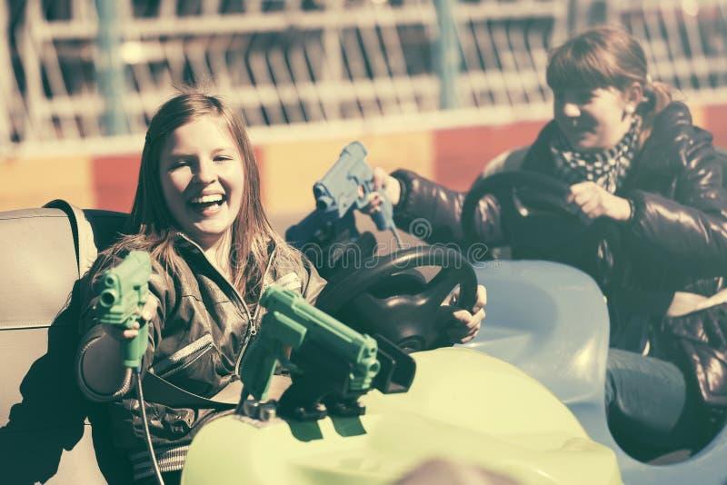 Entraînement de l'adolescence heureux de deux filles voitures de butoir image libre de droits