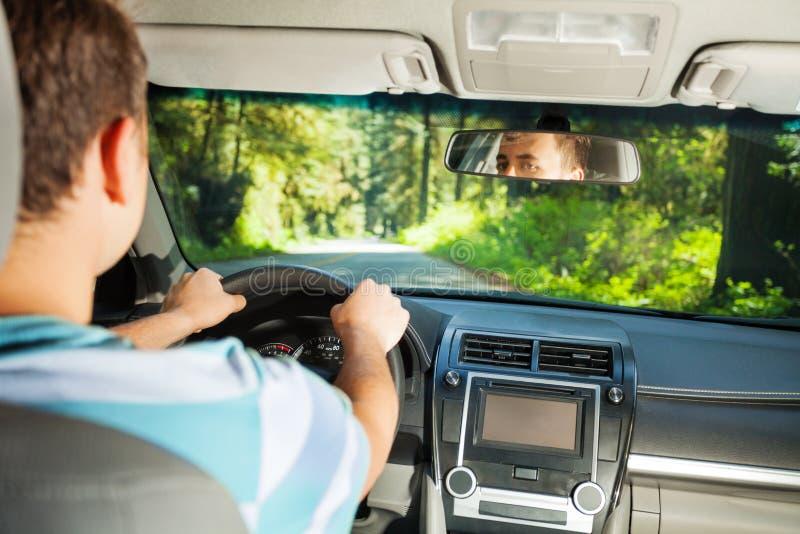 Entraînement de l'homme à l'intérieur de la voiture avec la belle vue de forêt photos stock