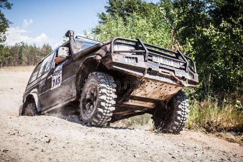 Entraînement de voiture de course tous terrains lourd le long de la route poussiéreuse image stock