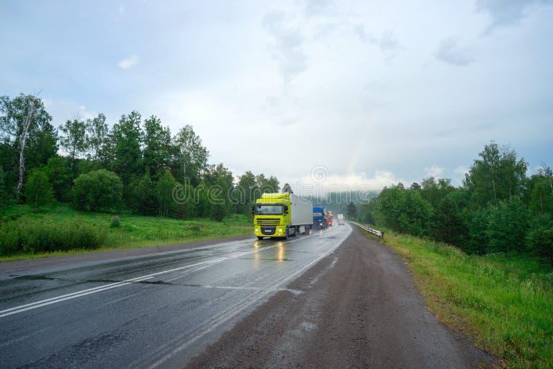 Entraînement de voitures sur la route de montagne dans les Monts Oural sous la pluie photo libre de droits