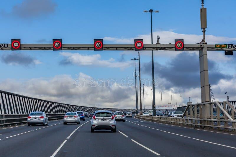 Entraînement de voitures sur le pont occidental en porte passant le panneau routier de 80 kmh photo stock