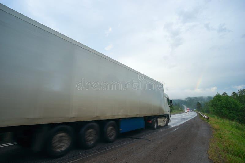 Entraînement de voitures sur une route de montagne dans les Monts Oural sous la pluie images stock
