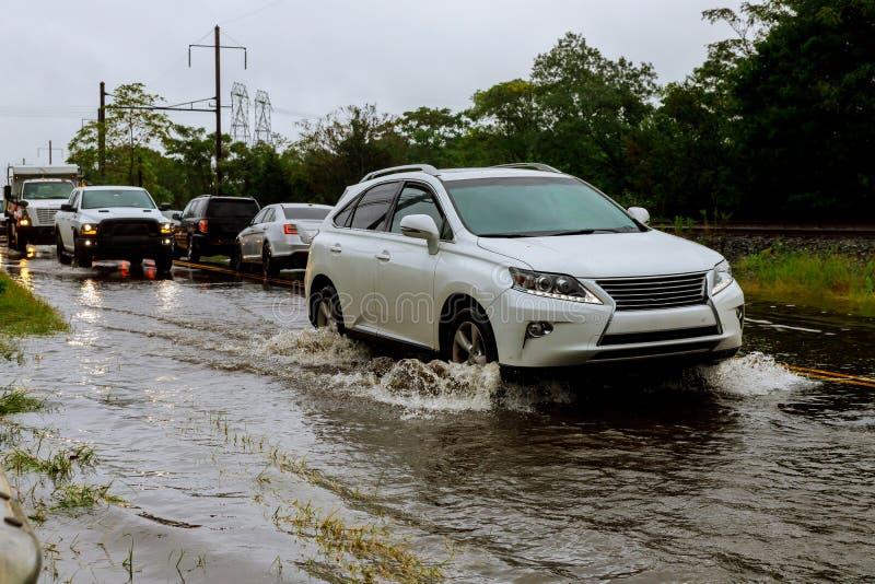 entraînement de voitures sur une route inondée pendant une forte pluie d'inondation, image stock