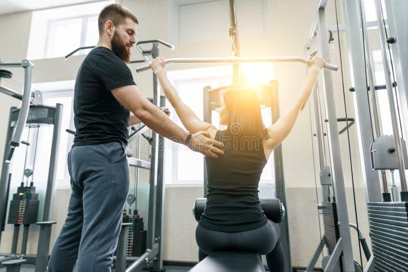 Entraînement personnel d'entraîneur de forme physique et femme de aide de client faisant l'exercice dans le gymnase Sport, travai image libre de droits