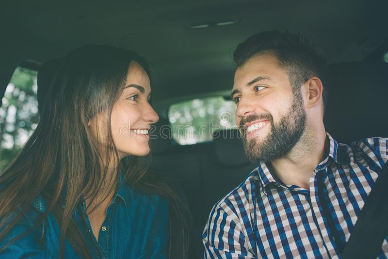 Entraînement soigneux Beaux jeunes couples se reposant sur les sièges de passager plan et souriant tandis qu'homme bel conduisant image libre de droits