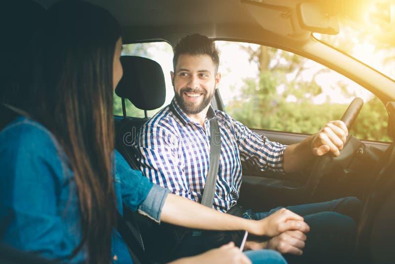 Entraînement soigneux Beaux jeunes couples se reposant sur les sièges de passager plan et souriant tandis qu'homme bel conduisant photo stock