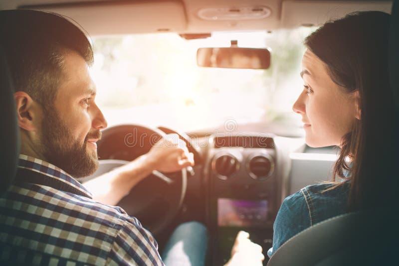 Entraînement soigneux Beaux jeunes couples se reposant sur les sièges de passager plan et souriant tandis qu'homme bel conduisant photos libres de droits