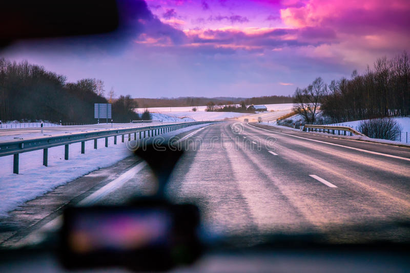 Entraînement sur l'autoroute pendant l'hiver au coucher du soleil image libre de droits