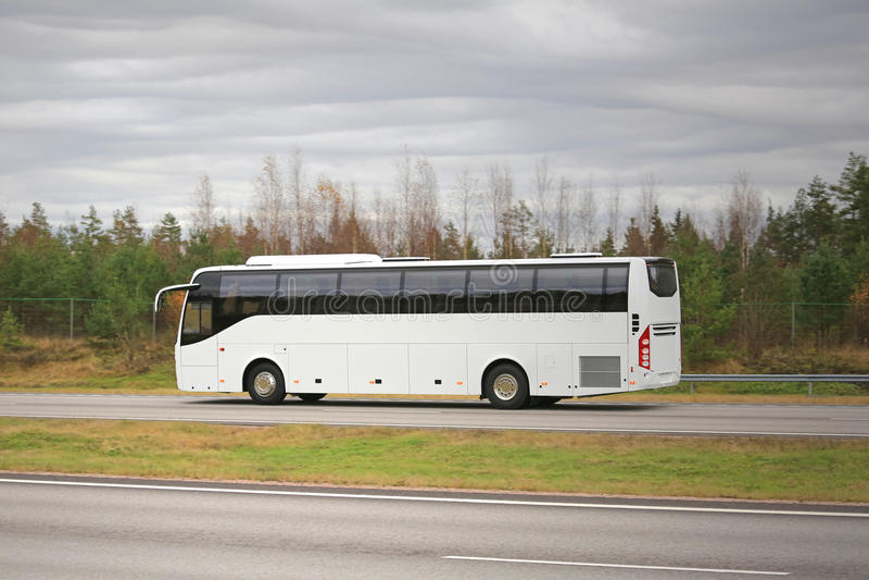 Entraîneur blanc Bus sur l'autoroute un jour nuageux photographie stock libre de droits