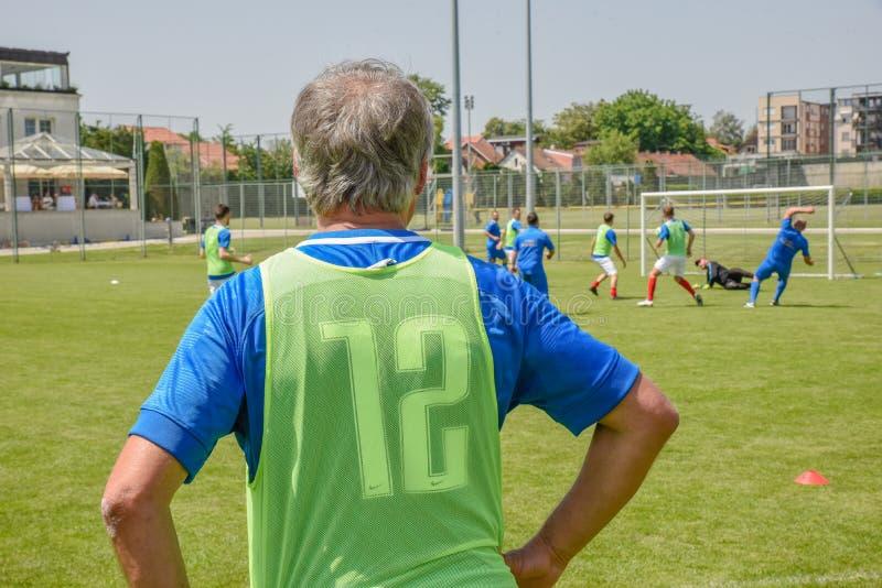Entraîneur d'une jeune équipe de football par le lancement image libre de droits