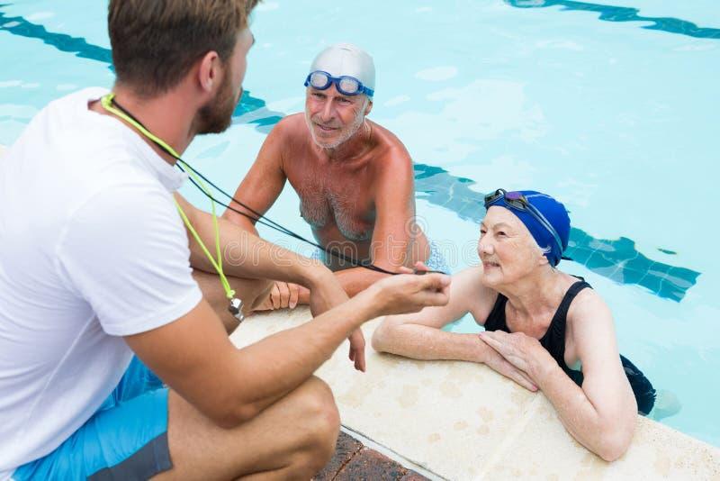 Entraîneur de bain montrant le chronomètre aux couples supérieurs images stock